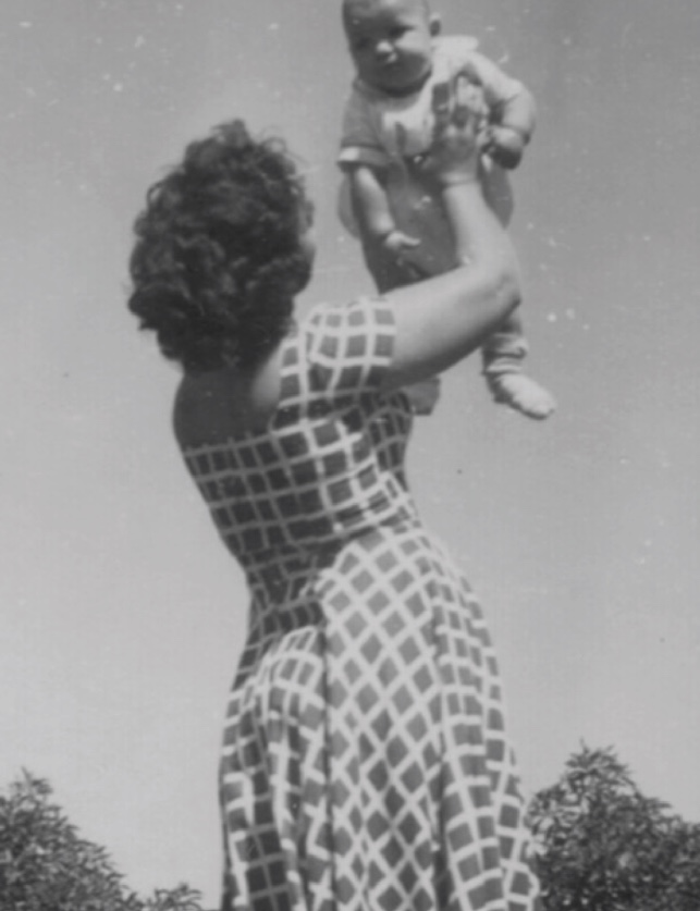 an old image of a woman holding a baby in the air