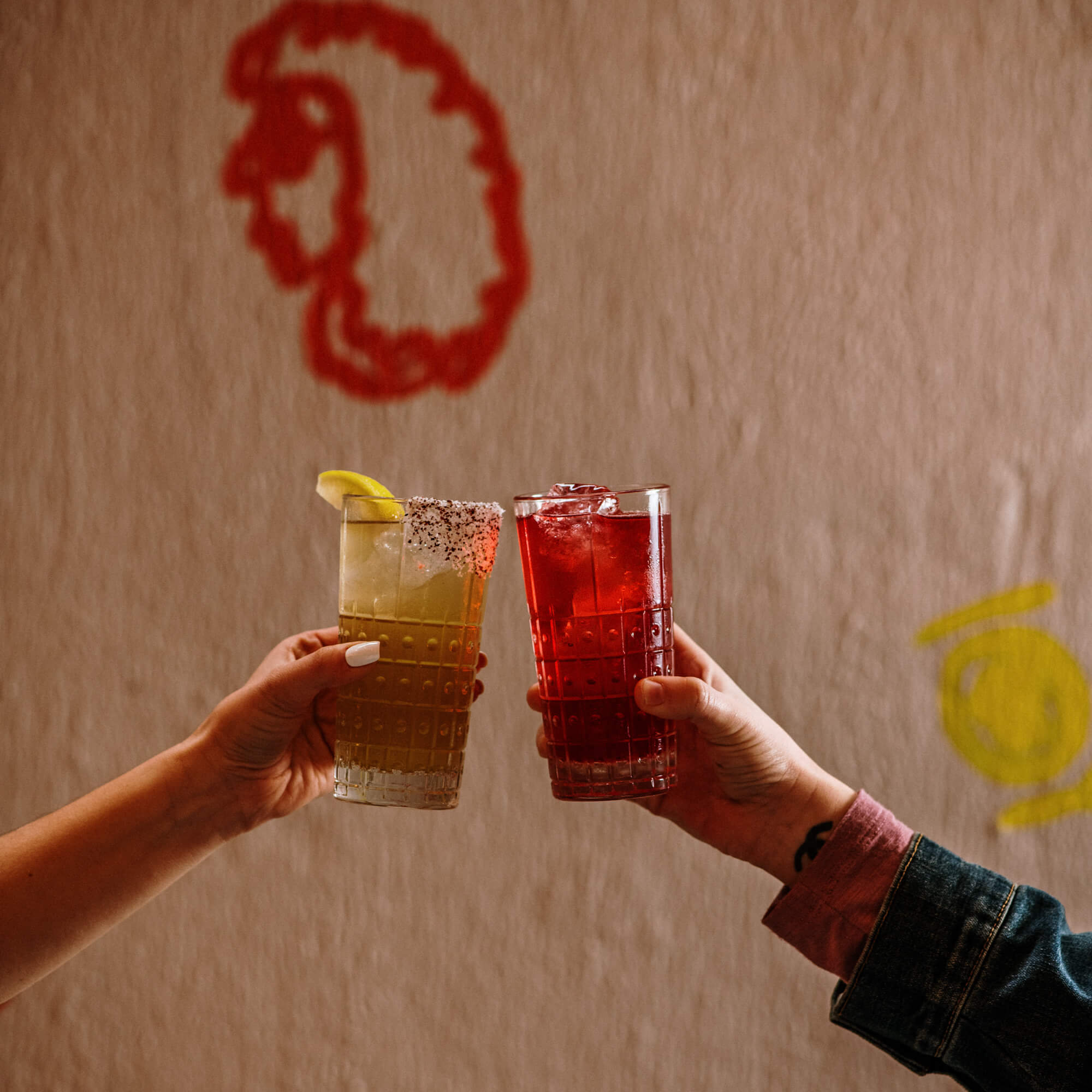 two hands holding cocktails