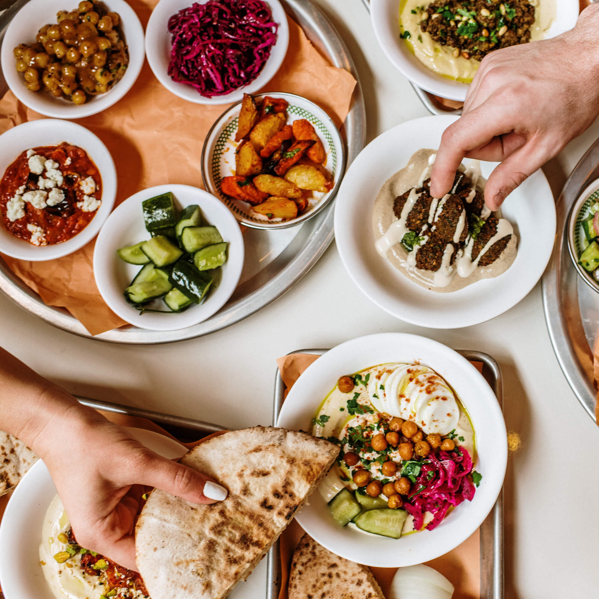 two hands eating an assortment of Mediterranean food dishes
