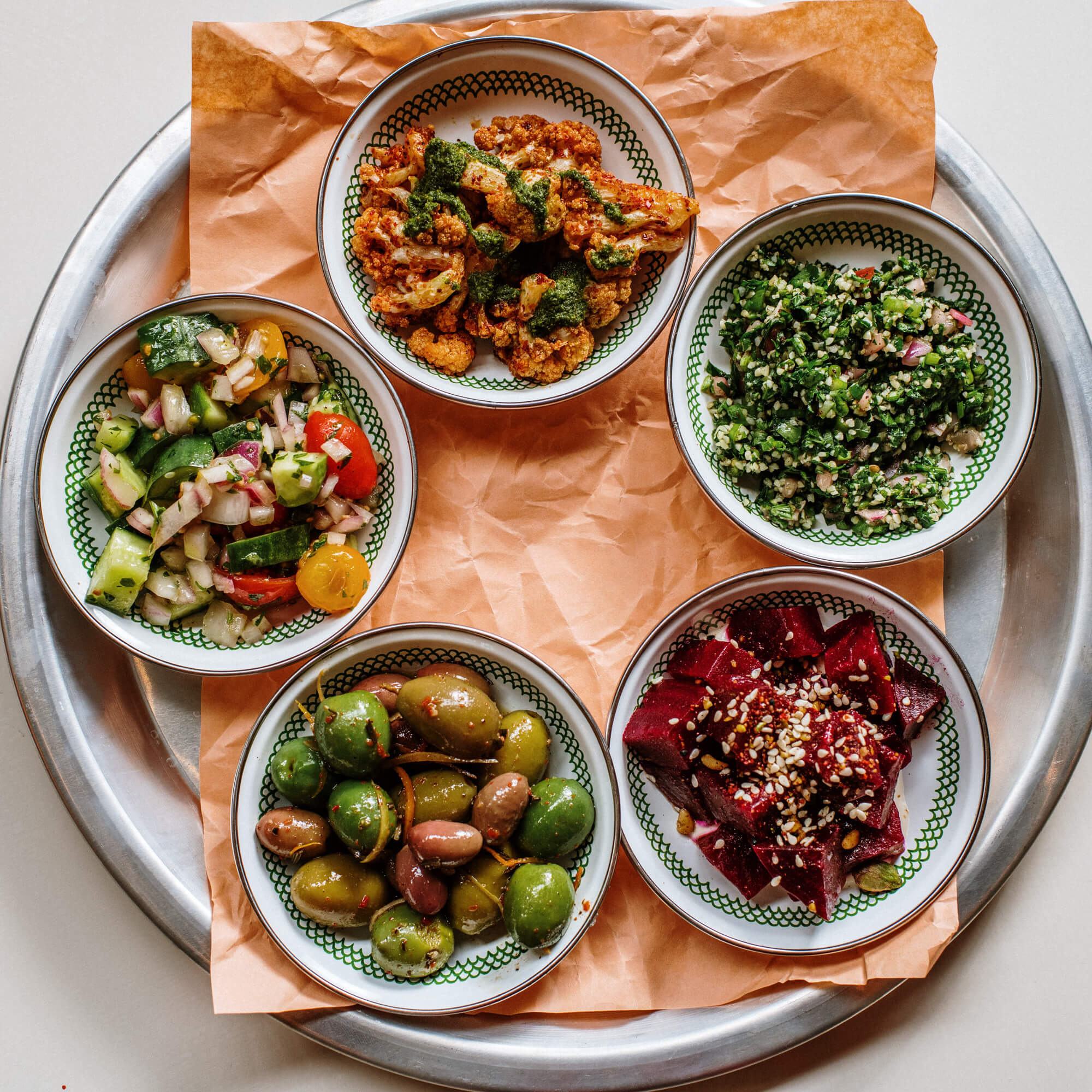 a tray of four mediterranean side dishes